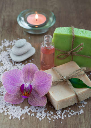 Aromatherapy bottle, orchids and handmade soap bars photo