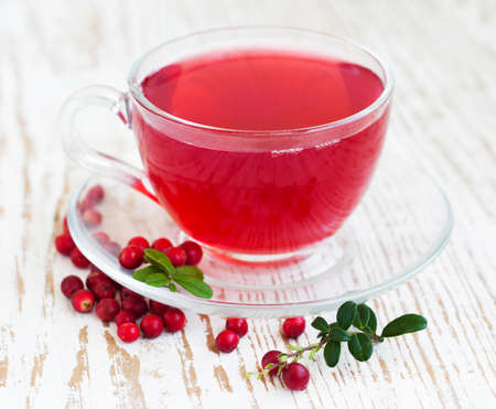Cranberry tea in a glass cup on a wooden background photo