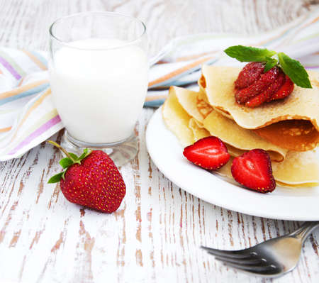 Pancakes with  strawberries  and milk on a wooden  background photo