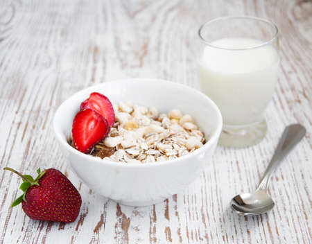A bowl of cereal with strawberries and  milk photo