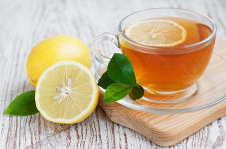 taza de te: Taza de té con limón en una mesa de madera