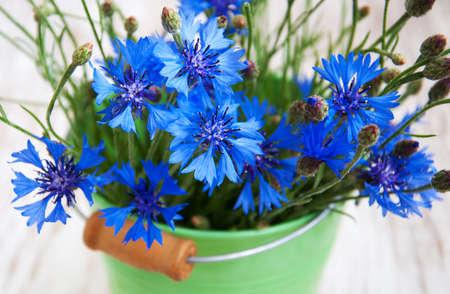 Bucket of Cornflower bouquet  on a wooden  background photo