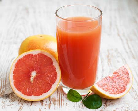 Grapefruitsaft und reife Grapefruits auf einem hölzernen Hintergrund
