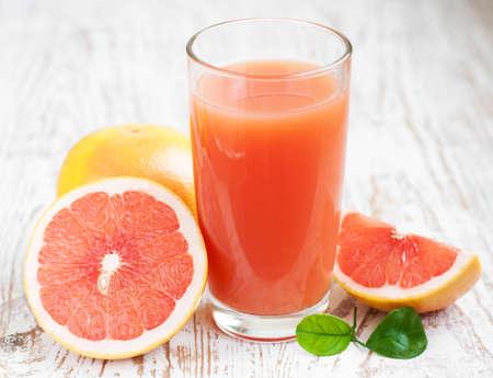 sappen: Grapefruitsap en rijpe grapefruits op een houten Stockfoto