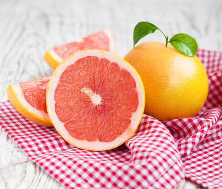 ripe grapefruits with leaves  on wooden  background