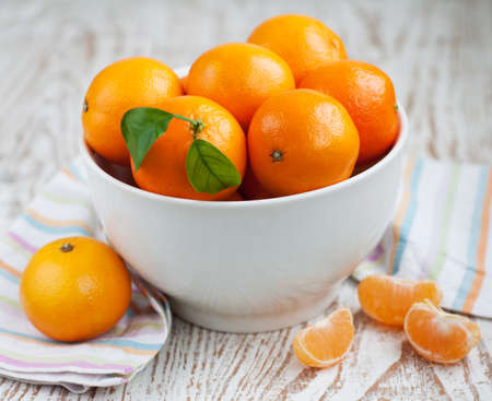 Bowl of fresh tangerines on a wooden  photo