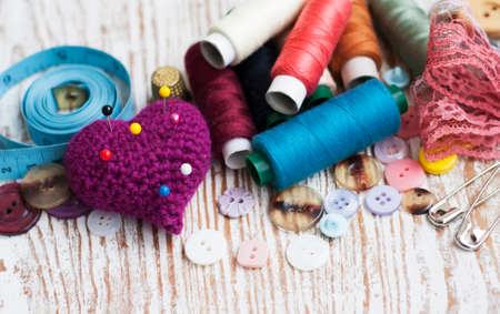 large group of items: threads, measuring tape, pins, buttons on a wooden background