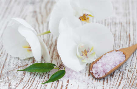 bathsalt: bathsalt, orchid  and green leaves on a wooden background Stock Photo