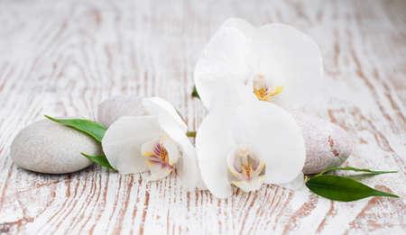réglage de Spa avec des pierres de massage et orchidée blanche
