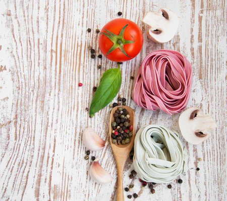 A arrangement of  pasta, garlic, tomatoes    on a wooden  background photo