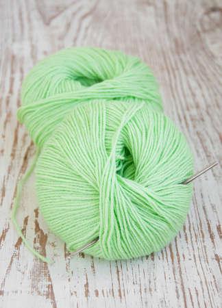crotchet: Green yarns and crotchet hook on a wooden