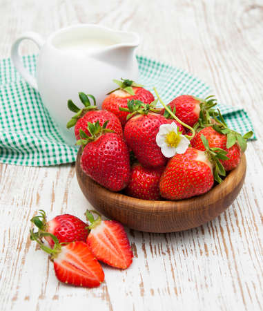 Bowl with ripe strawberry, jug of milk  on old wood table photo