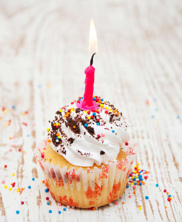 Tasty birthday cupcake with candle on wooden table photo