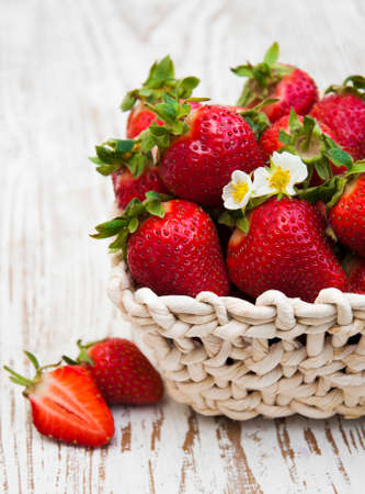 fresh sweet ripe strawberries in a basket on a wooden table photo