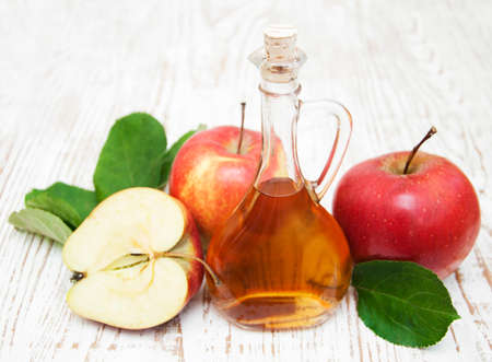 green bottle: Apple cider vinegar and fresh apple on a wooden background Stock Photo