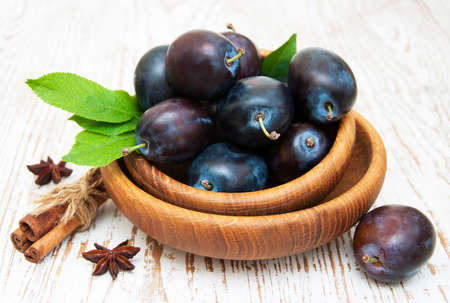 ingradient: Fresh purple plums in a bowl on the wooden background Stock Photo