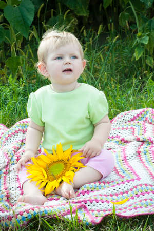 Beautiful baby  with sunflower in summer field photo