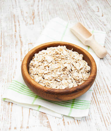 Bowl of oats on a old wooden background photo