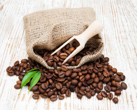 Coffee beans on burlap sack with scoop photo