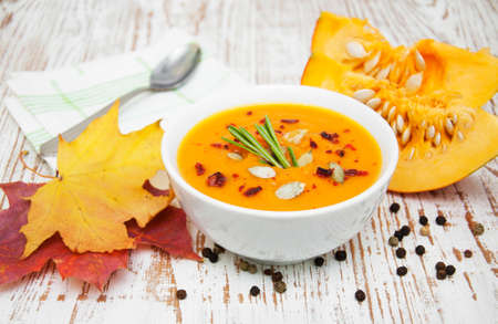 bowl with pumpkin soup on a wooden background photo