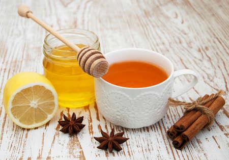 frischem Honig und eine Tasse Tee mit Gewürzen und Zitrone auf Holzuntergrund