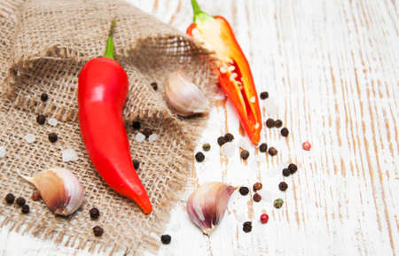 bulb and stem vegetables: Garlic with peppers on a wooden background