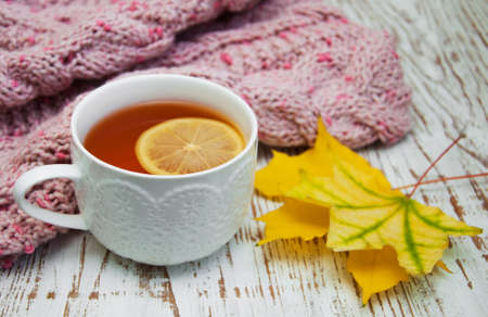 Autumn time: cup of hot tea with lemon and scarf photo