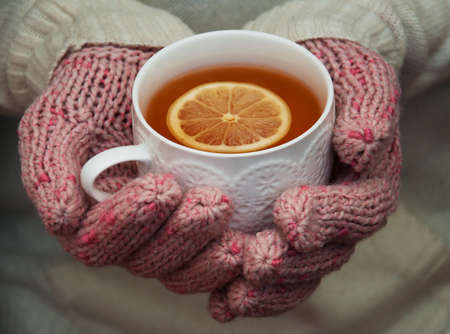 Girl in winter clothing holding cup with hot tea