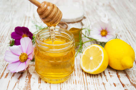 Jars of honey and lemons on wooden table photo