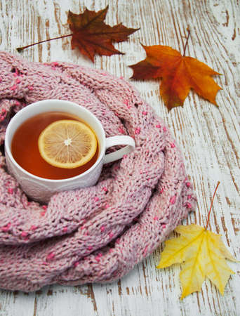 cold beverages: Autumn time: cup of hot tea with lemon and scarf