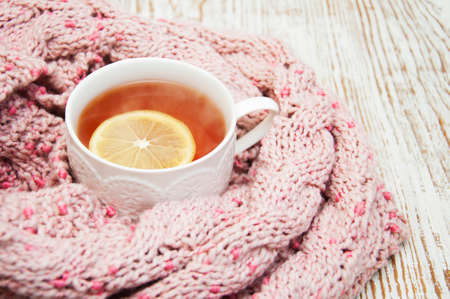 autumn food: Winter time: cup of hot tea with lemon and scarf