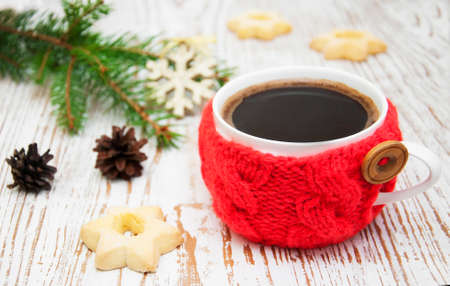Christmas setting with knitted  mug of  coffee on a rustic wooden background photo