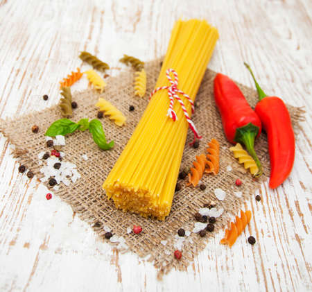 Italian ingredients - pasta, vegetables, spices on a  wooden background photo