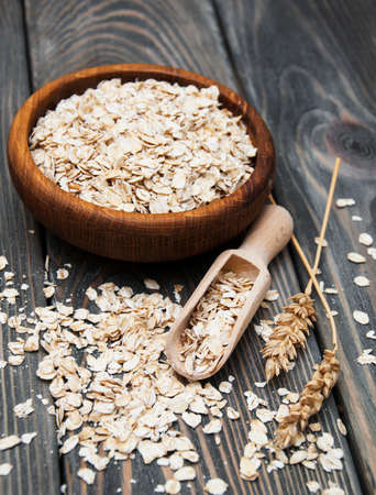Wooden bowl with oat on a wooden background photo