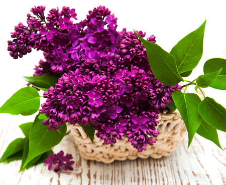 summer lilac flowers in basket on a wooden background photo