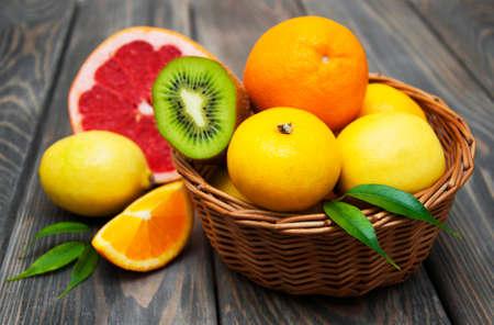 cesta de frutas: Cesta de C�tricos en un fondo de madera Foto de archivo