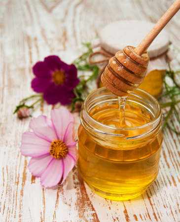 honey pot: Glass pot of sweet honey with flowers on wooden table