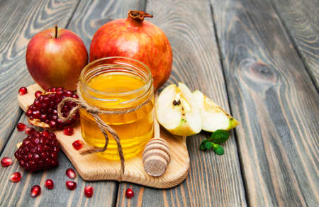 honey apple and pomegranate on wooden table photo