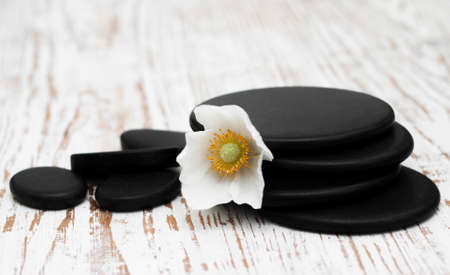 stones with flower: Spa stones,  flower heads on a wooden background Stock Photo