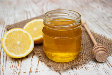 Jars of honey and lemons on wooden table