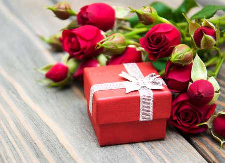 Rote Rosen und Geschenk-Box auf einem hölzernen Hintergrund
