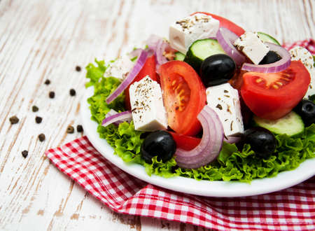 Plate with Fresh Greek salad on a wooden background Stock Photo