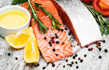 portions: portions of fresh salmon fillet with aromatic herbs, spices and vegetables Stock Photo