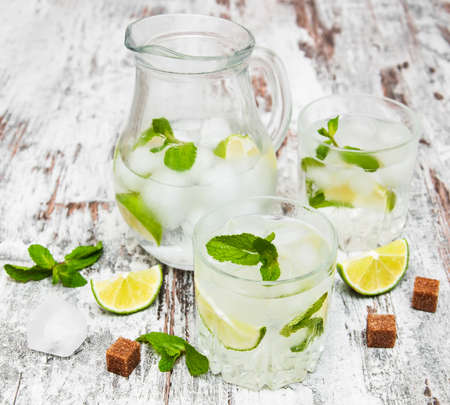 Cold fresh lemonade drink on a wooden background photo