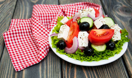 Plate with Fresh Greek salad on a wooden background photo