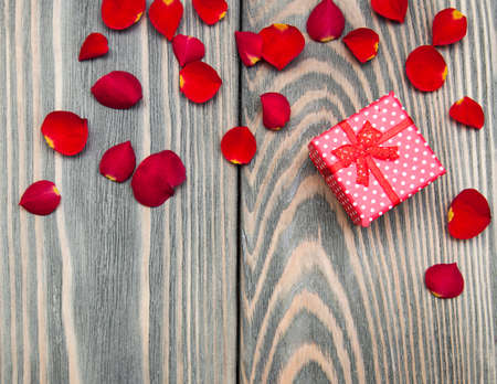 gift box and roses petals on a wooden background photo