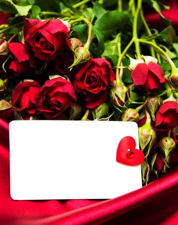 ramo de flores: Rosas rojas con la tarjeta de felicitaci�n en un fondo de seda Foto de archivo