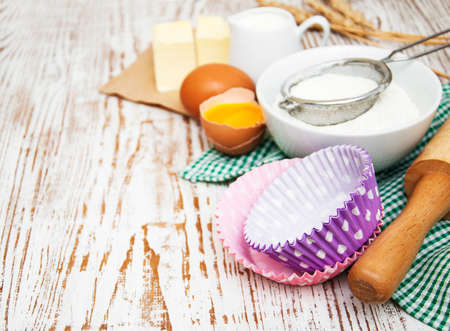 Baking ingredients - eggs, flour, and butter on a wooden background Imagens