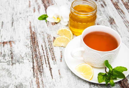 blossom honey: Cup of tea with lemon and honey on wooden background