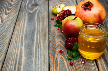 jewish cuisine: honey  apple and pomegranate on a wooden table